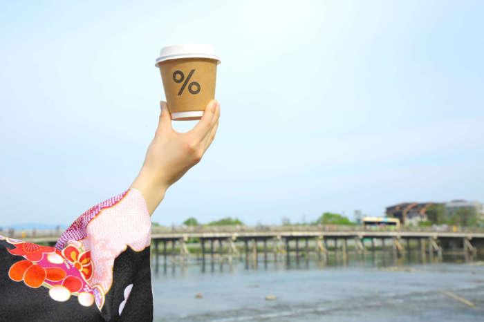 渡月橋を背景にアラビカコーヒーを持つ姿
