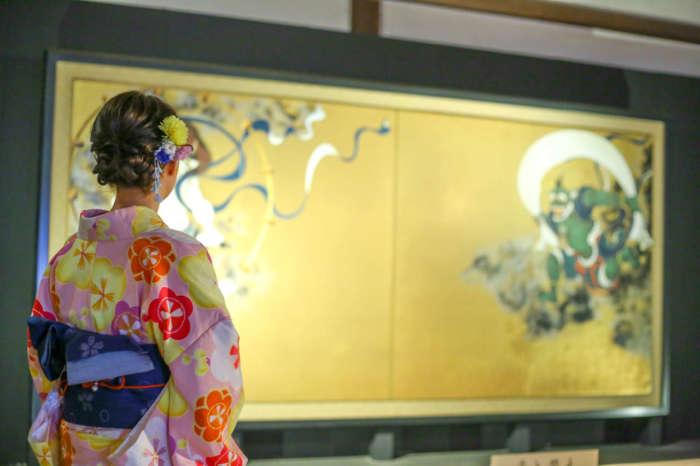 俵屋宗達作の「風神雷神図屏風」を鑑賞する着物姿の女性