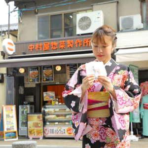 中村屋惣菜製作所前でコロッケを手に持つ着物姿の女性