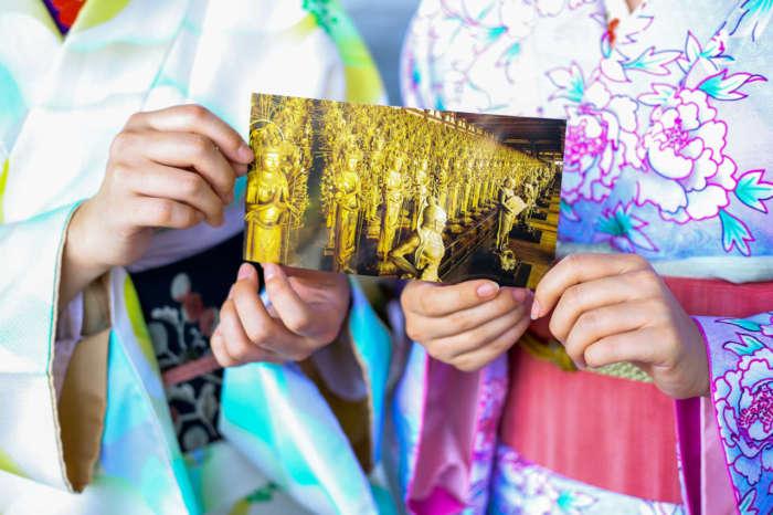 ポストカードを手に持つ着物姿の女性