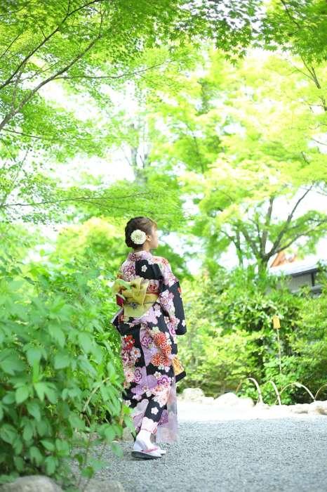 天龍寺の緑の中を着物姿で歩く様子